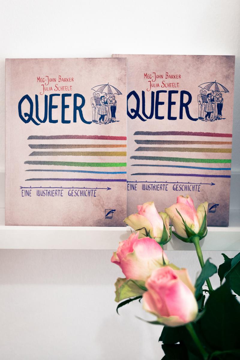 """Zwei Ausgaben des Buches """"Queer"""" stehen aufrecht mit dem Cover nach vorne im Regal."""