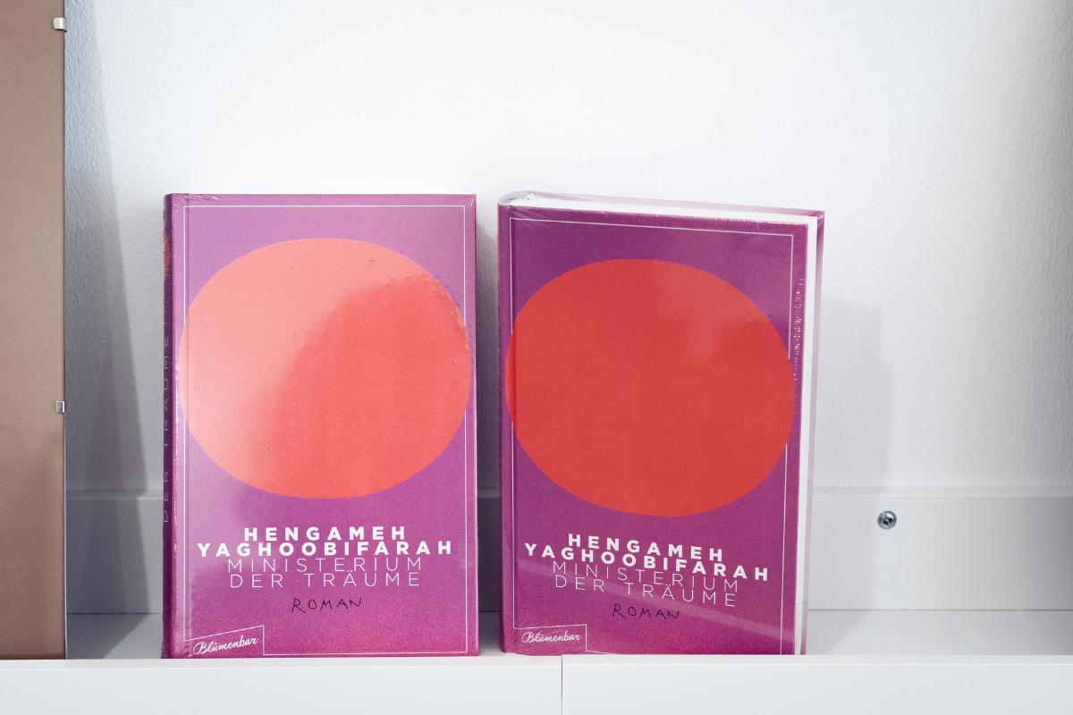 """Zwei Ausgaben vom Buch """"Ministerium der Träume"""" stehen auf dem Regal mit dem Cover nach vorne"""